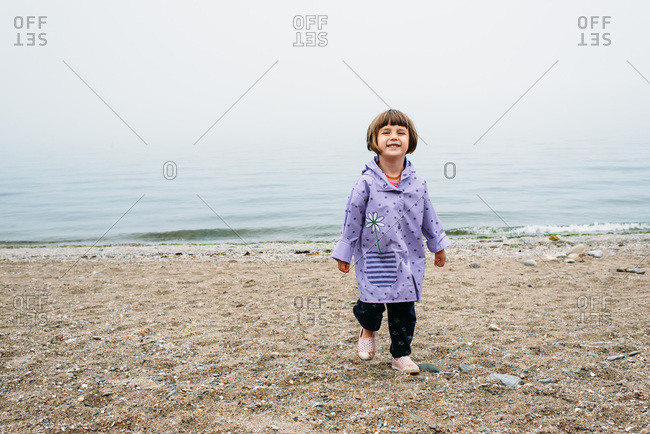 Little girl in purple rain jacket smiling on a foggy beach
