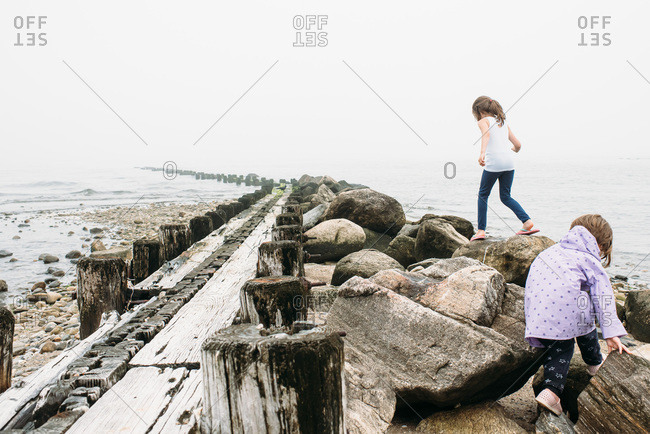 Girls playing on rocks at a foggy beach in Connecticut