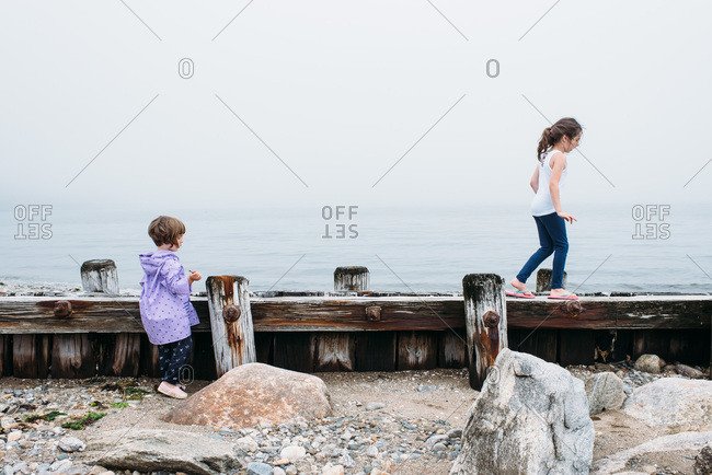 Girls playing on pier at a foggy beach in Connecticut