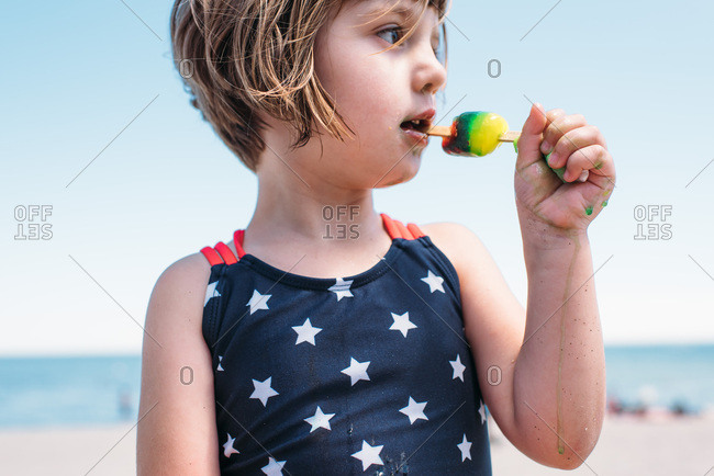 Little girl eating a messy, melting popsicle at the beach