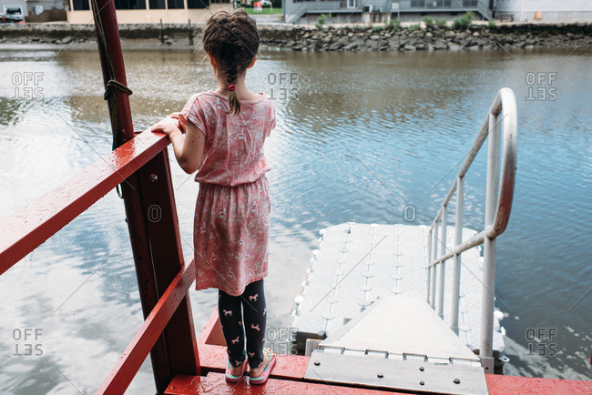 Young girl standing on the edge of a raised dock, looking down at the water