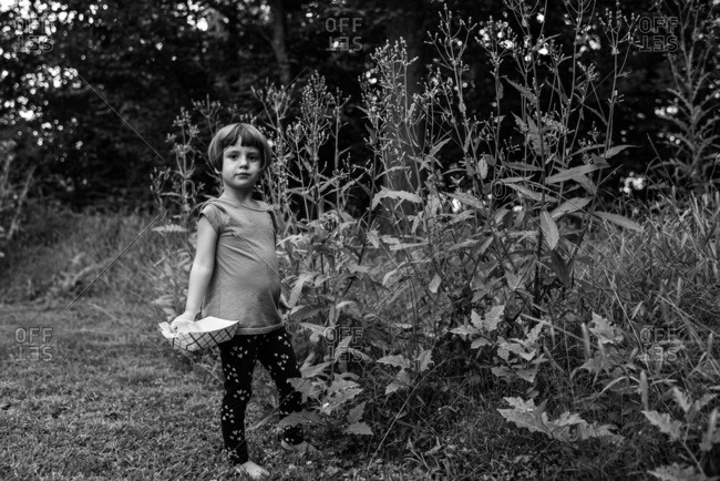 Little girl standing next to large weeds outside and looking at viewer