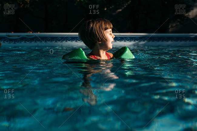 Little girl wearing floaties floating in swimming pool in beautiful light