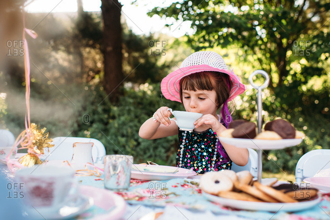 Dressed up little girl carefully sipping tea at a tea party
