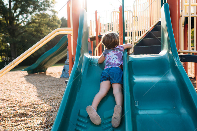 Little girl playing on a slide at a playground at golden hour