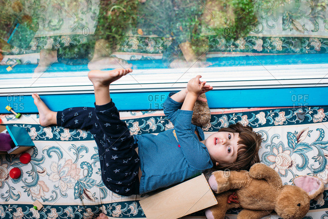 Little girl lying on a cushioned bench by a window with bare feet