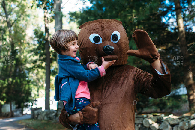 Man wearing a bear costume holding a happy little girl who is touching the costume