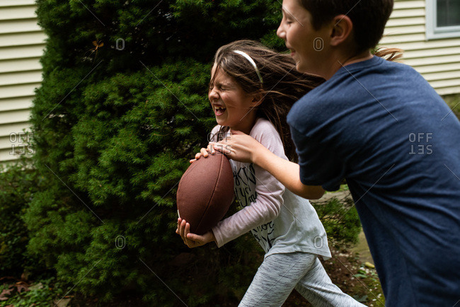 Boy grabbing football from girl as they run outside