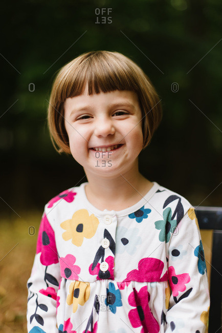 Portrait of a young girl in a floral dress in the woods