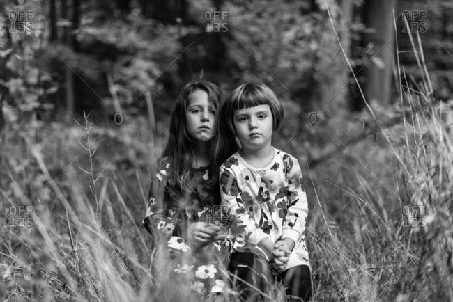 Portrait of sisters in coordinating floral dresses in the woods in black and white