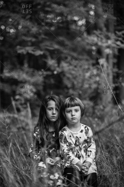 Two sisters in coordinating floral dresses in the woods