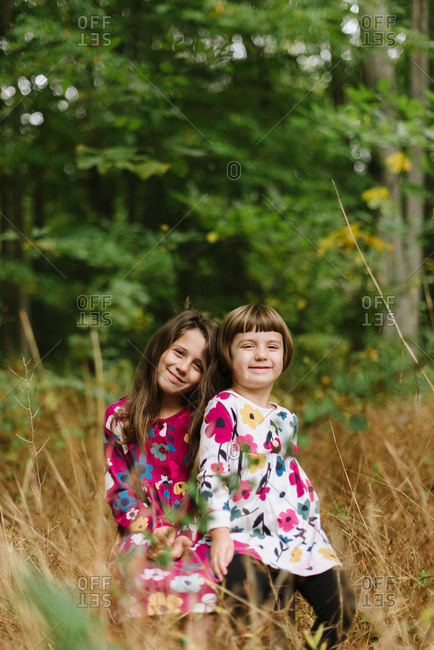 Portrait of sisters in coordinating floral dresses in the woods