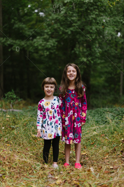 Portrait of happy sisters in coordinating floral dresses in the woods
