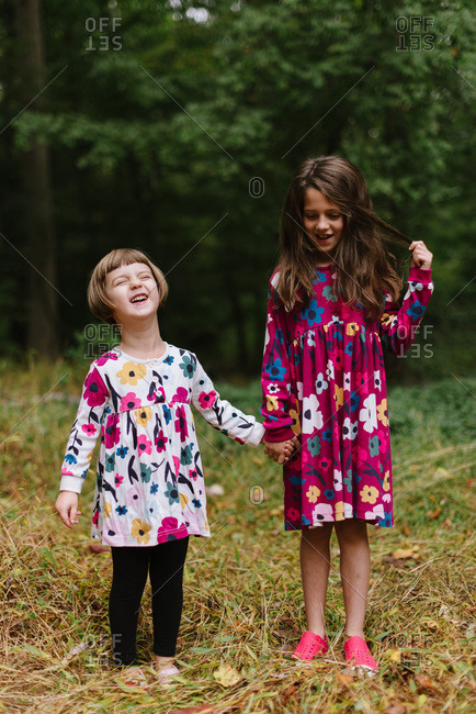 Two happy sisters in coordinating floral dresses in the woods