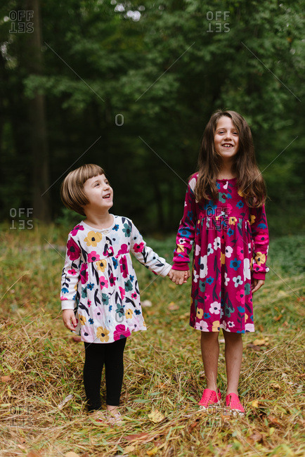 Two happy sisters in coordinating floral dresses in the forest