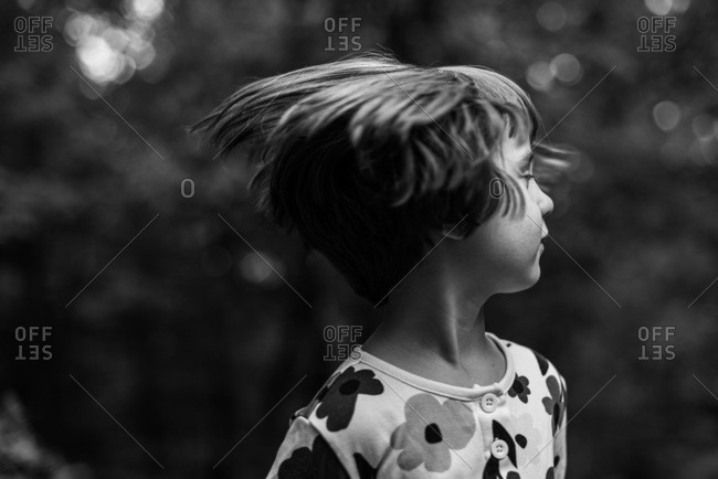 Little girl shaking her hair in the woods