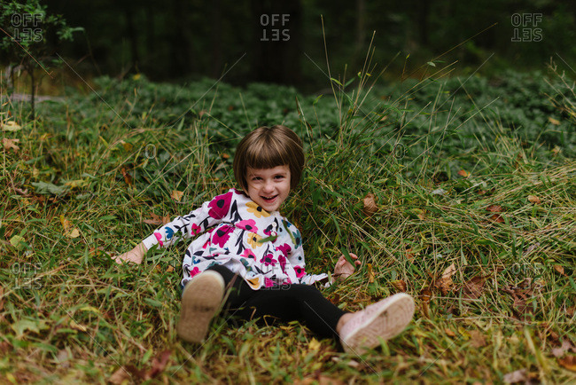 Smiling little girl falling down in some tall weeds