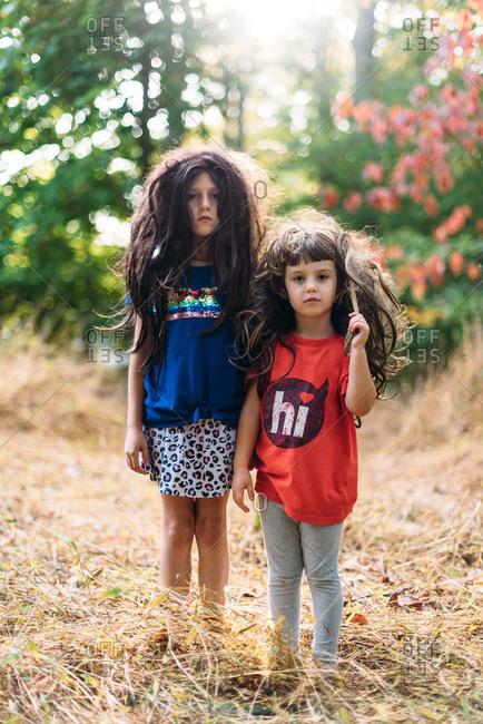 Portrait of sisters in wigs outside