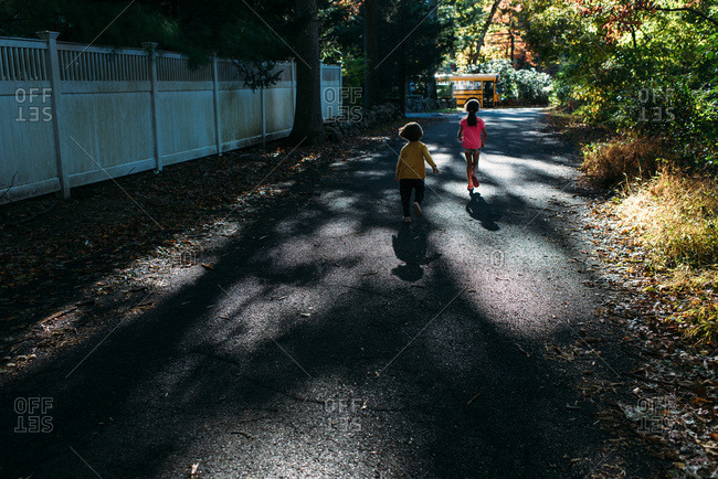 Two little girls running through dappled light down a street towards a yellow school bus