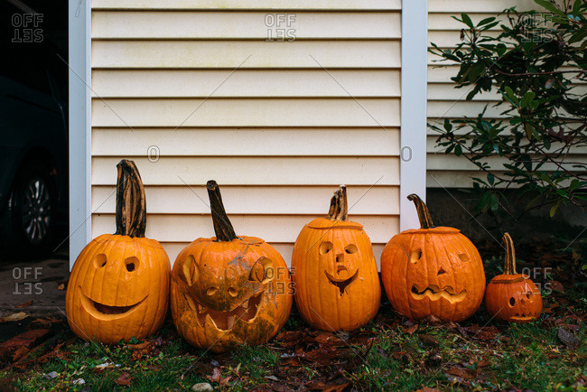 Jack-o-lanterns lined up by the side of a house