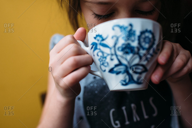 Little girl drinks from a blue and white teacup against a yellow wall