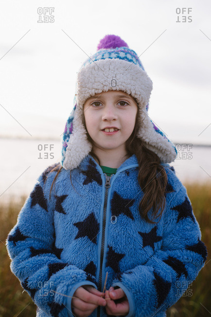 Portrait of a little girl wearing a winter hat at the beach