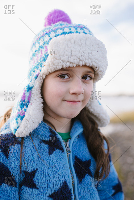 Close up of a little girl wearing a winter hat at the beach