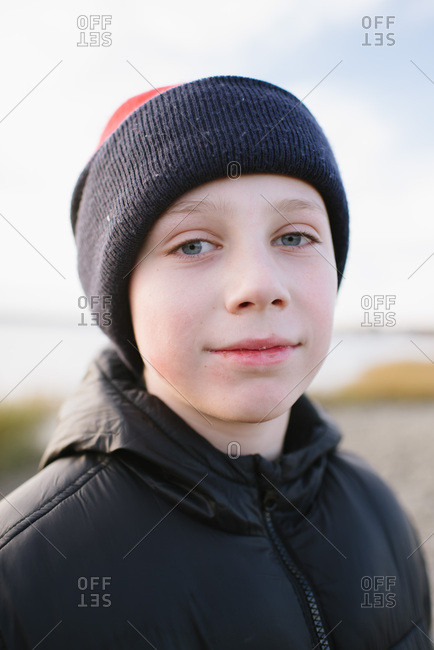 Portrait of a young boy with blue eyes wearing a winter hat and jacket at the beach