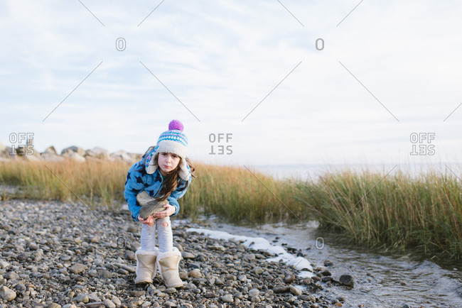 Young girl in a winter hat carrying a big rock on a rocky beach