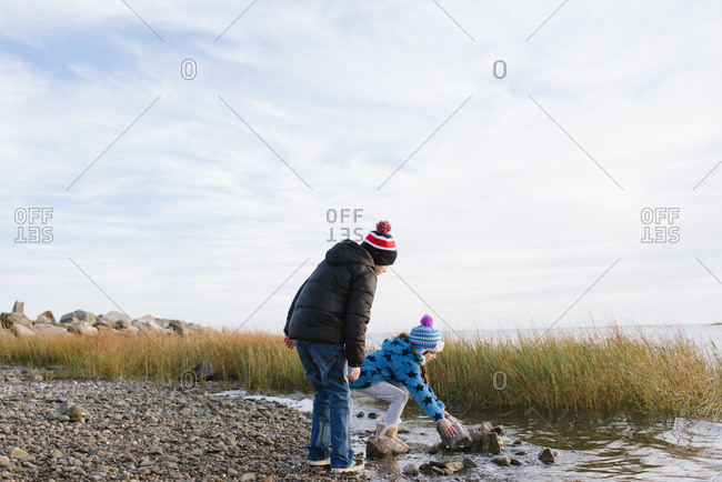 Young siblings working together to carry a heavy rock on a beach in winter
