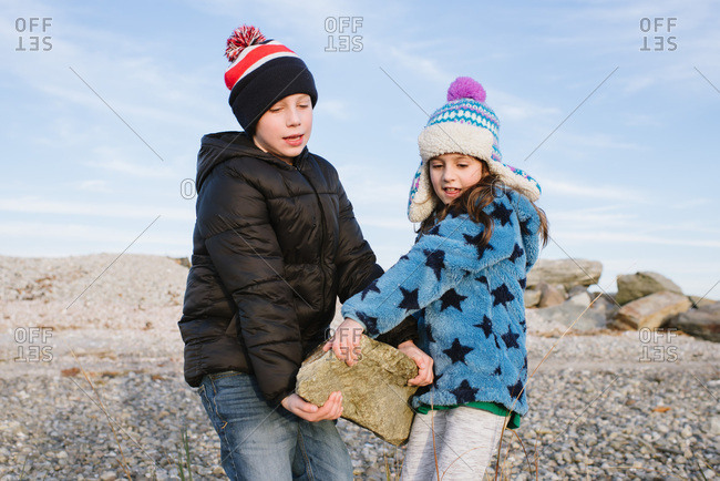 Young boy and girl working together to carry a heavy rock on a beach in winter