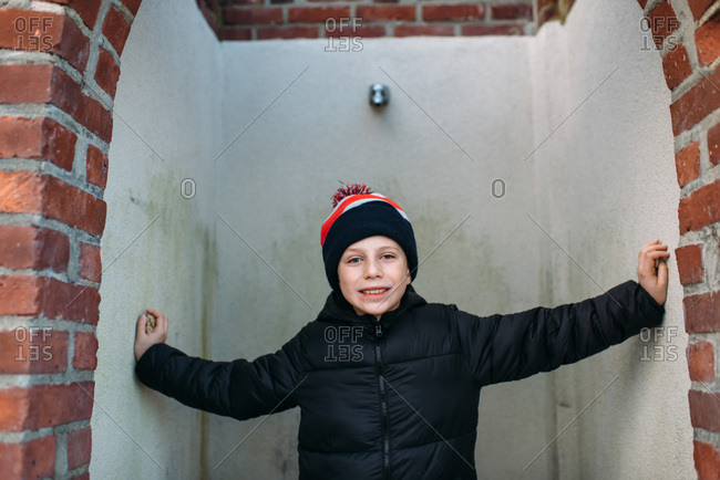 Smiling boy in winter gear standing with arms outstretched in an outdoor shower