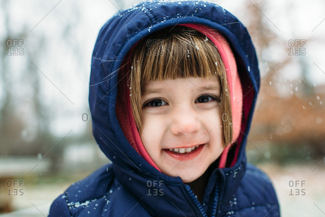 Close up portrait of a little girl smiling in the snow
