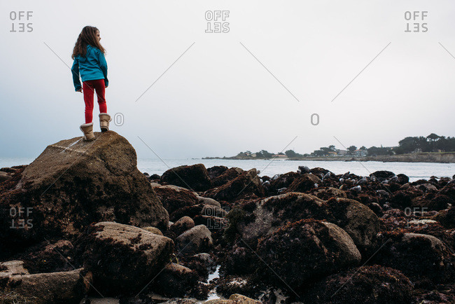 Young girl standing on rocks overlooking the ocean