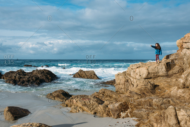 Young girl standing on rocks pointing out to the ocean