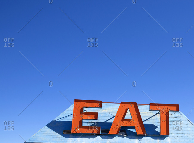 """Deserted cafe sign saying """"EAT"""" on the Highway to Las Vegas in the California desert"""