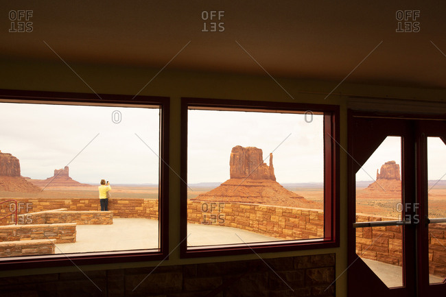 Tourist taking pictures of Monument valley stone formations in Navajo Tribal park,
