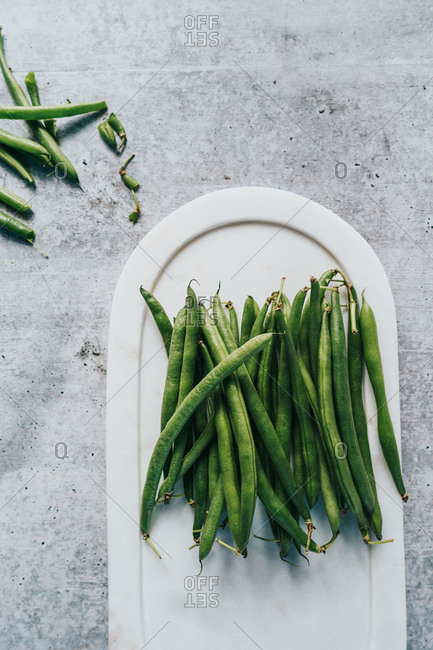 Overhead view of green beans on white plate