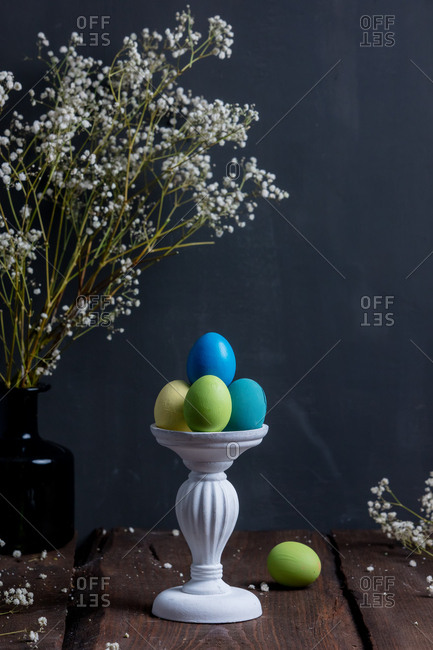 Easter eggs on stand near flowers on wooden table
