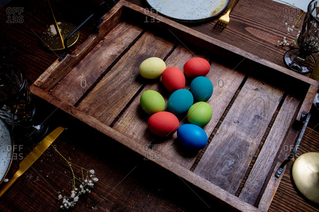 Easter eggs on tray on a wooden table, from above