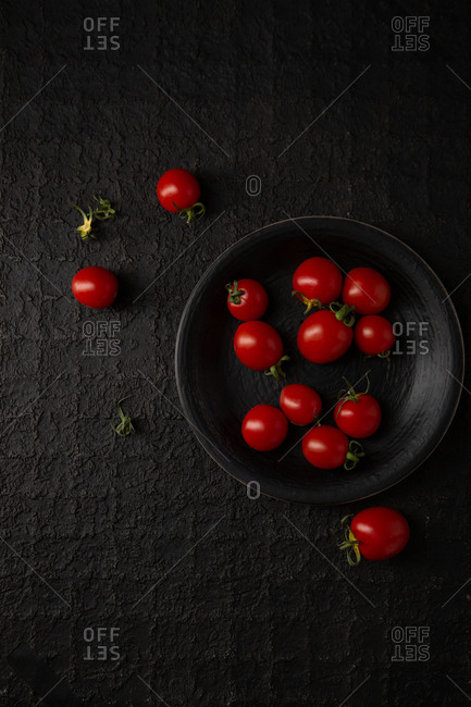 Red tomatoes in a black bowl on black surface