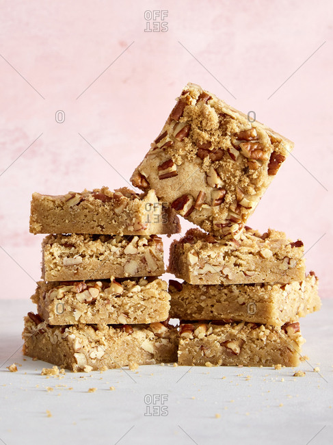 Pecan blondie cookie squares in front of a pink background
