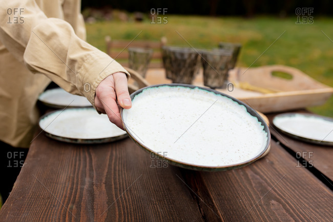Woman placing plates on the table before dinner