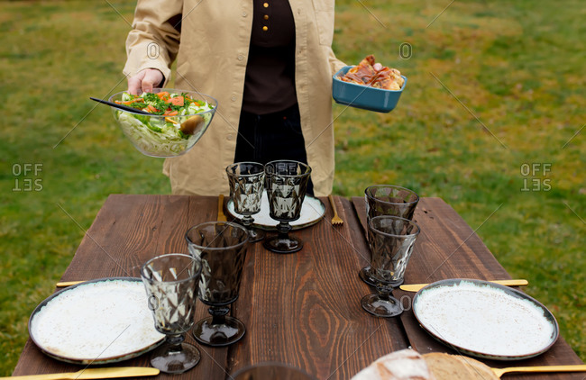 Woman lays out food on a table in backyard before dinner