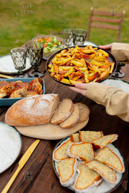 Woman puts fried potatoes on a dinner table in backyard