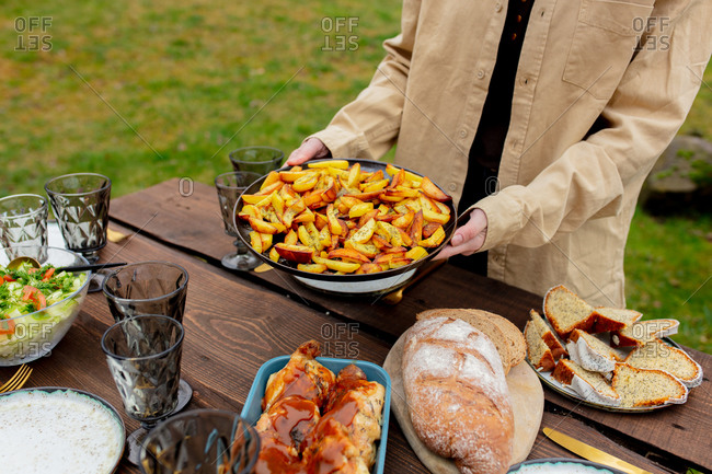 Woman placing fried potatoes on a dinner table in backyard