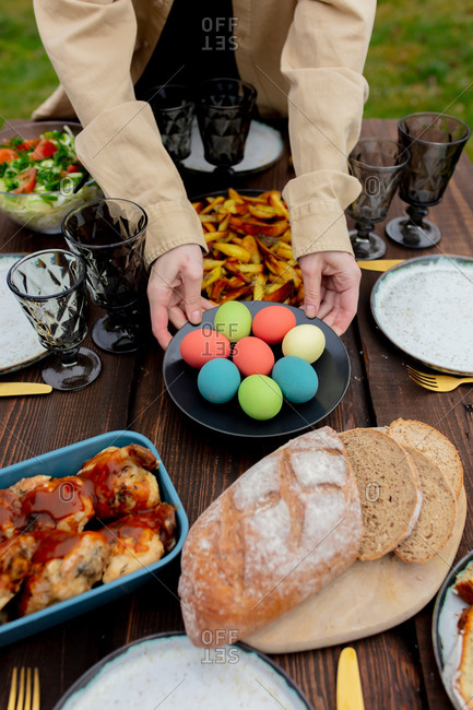 Woman placing eggs on table with food at Easter dinner in backyard