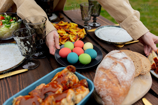 Woman placing eggs on Easter dinner table in backyard