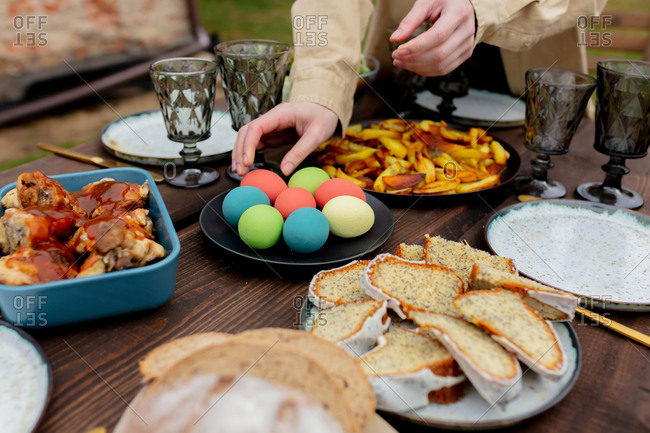 Woman placing food and Easter eggs on dinner table in backyard