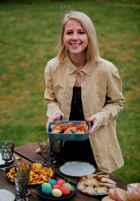 Woman placing out food on a Easter dinner table in backyard